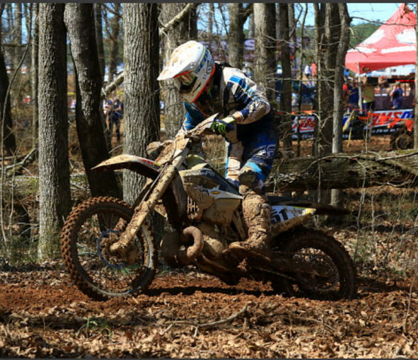 Evan Earl flying through the woods at a GNCC race
